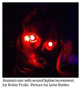 "Picture is dark and shows two glowing red eyes shining in a skull face covered with what appears to be dried skin. The eyes are reflecting onto strands of hair that partially cover one eye. The head is tilted. The caption says ""Animatronic with sound/lights/movement, by Robin Frolic. Picture taken by Livia Statler."""